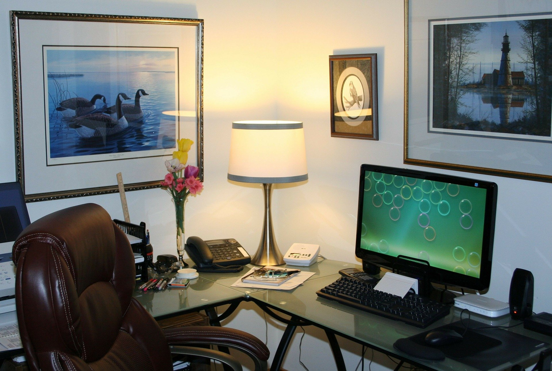 A home office, including hanging pictures, a computer on a desk and an office chair